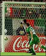 Mohammed Al-Deayea looks on in dismay as Damien Duff's shot slips through his hands and into the net