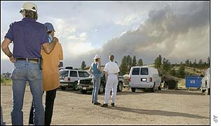 Larry Landis (left) puts his arm on the shoulder of his wife, Rea, as they watch the fire approach their new home west of Colorado Springs