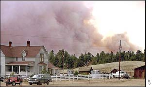 Fire and smoke loom rise behind the Twin Creek Ranch just north of Highway 24 in Florissant, Colorado