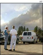 As a plume of smoke rises from in the mountains north of Florissant, Colorado