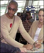 Thierry Henry checks in for his flight home with his girlfriend
