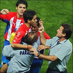 Paraguay's Nelson Cuevas is mobbed by team-mates and coaches after hitting the winner