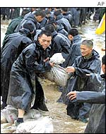 Police officers in the northwest Shaanxi province form a human chain to place sandbags in a river
