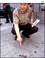 Lee Sang-min, journalist from South Korean news agency Yonhap, points at blood stains that he said resulted from the struggle