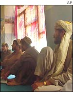 Afghans watch the live broadcast of the loya jirga
