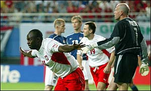 Emmanuel Olisadebe celebrates scoring his opener for Poland