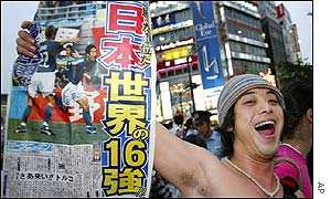 A fans shows off the front page of the newspaper in Tokyo's crowded streets