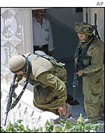 Israeli soldiers carry out a house search