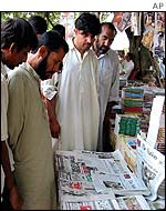 Karachi residents read newspapers