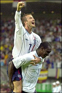 Beckham celebrates England's third goal with scorer Emile Heskey