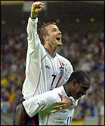 David Beckham hitches a ride on Emile Heskey after laying on England's third goal