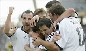 German players mob Oliver Neuville after his goal against Paraguay