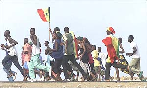 Fans carrying the national flag run through Dakar after Sunday's game against Sweden