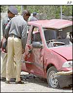 Policemen inspect car damaged in the consulate bombing
