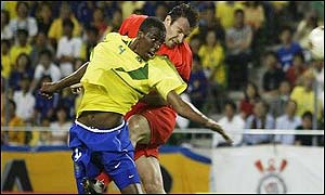 Roque Junior and Marc Wilmots climb for the ball
