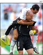 Landon Donovan's jumps on the back of US keeper Brad Friedel