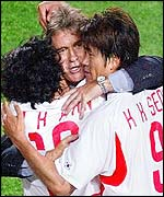 Guus Hiddink (C) hugs midfielder Ahn Jung-hwan (l) and forward Seol Ki-hyeon (r)  after South Korea's victory.