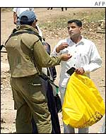An Israeli soldier questions a Palestinian man at a checkpoint