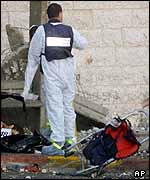 An Israeli forensic expert covers a body at the scene of the explosion