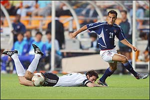 Germany's Christoph Metzelder is felled by the USA's Landon Donovan