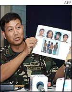 Major General Ernesto Carolina holds a picture of the rebels captured