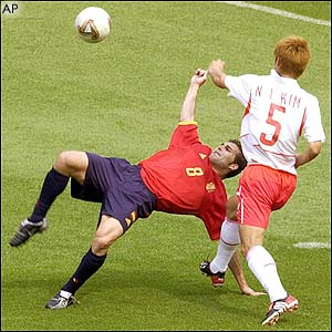 Spain's Ruben Baraja  attempts an overhead kick in front of South Korea's Kim Nam-Il