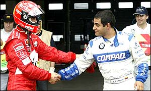 Michael Schumacher shakes the hand of arch rival Montoya after the Colombian won pole on the German's home turf