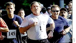 President George W Bush jogs with aides
