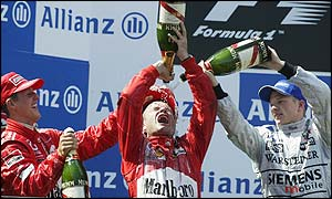 Michael Schumacher and Kimi Raikkonen drench Barrichello with champagne