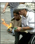 Palestinian youths light fire-bombs in Hebron