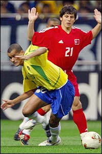 Brazil's Rivaldo goes down under the challenge of Turkey midfielder Emre Belozoglu