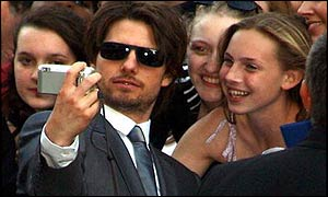 Tom Cruise takes a photo of himself with a fan