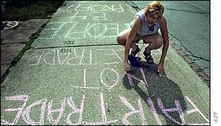 Student Karen Kaufman scrawls her anti-globalization message on a pavement during a G8 protest in Toronto