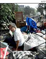 A woman sits amid her belongings after her home where she lived for 50 years was torn down