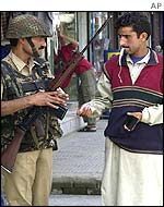 Soldier questions Kashmiri Muslim at checkpoint in Srinagar