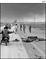 Iranian soldiers pass Iraqi bodies, February, 1986