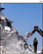 A digger sorting debris in Hebron
