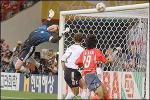 A looping volley from a South Korean player hits the crossbar as Kahn stretches to save