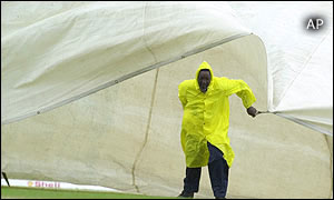 A grounds worker pulls a cover onto the field as rain falls in Grenada