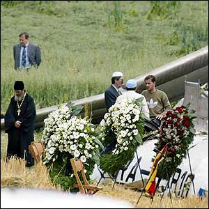 Priest and flowers at the crash site