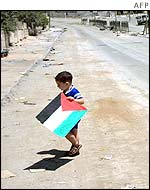 A boy alone in the street with a Palestinian flag