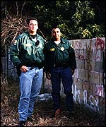 Police officers next to gang graffiti