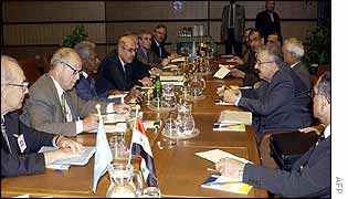 Kofi Annan (centre left) faces Iraqi Foreign Minister Naji Sabri during talks