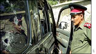 An Afghan policeman looks at the ambushed car