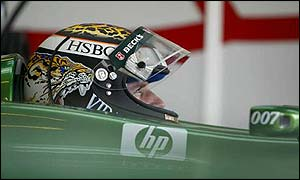 Eddie Irvine watches the action as he waits to go out for another run in the Jaguar