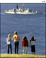 Children stand on Lord Howe Island to view the British warship HMS Nottingham