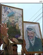 Palestinian protesters hold pictures of Yasser Arafat and the ousted Jibril Rajoub