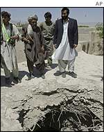 Afghan villagers inspect a hole said to be caused by a stray US bomb