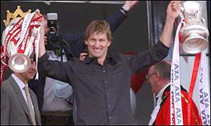 Arsenal captain Tony Adams shows off the Premiership and FA Cup trophies