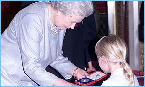 The Queen presents a silver medal to Louise, aged 8, from Dorking